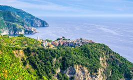Corniglia traditional typical Italian village with colorful buildings on rock cliff and Manarola, Genoa Gulf, Ligurian Sea, blue s. Ky background, National park royalty free stock photos