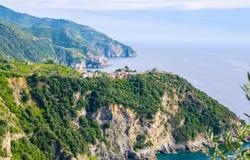 Corniglia traditional typical Italian village with colorful buildings on rock cliff and Manarola. Genoa Gulf, Ligurian Sea, blue sky background, National park stock image