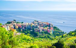Corniglia traditional typical Italian village with colorful multicolored buildings houses on rock cliff and boat on water of Genoa. Gulf, Ligurian Sea, National stock images