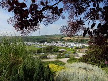 Cornish caravan park. Framed by trees and plants with view to Cornish caravan park, hills and blue sky royalty free stock photo