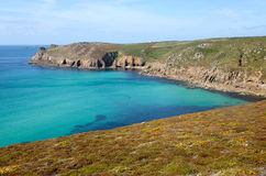Cornish coast path to Lands End. A turquoise see and colourful heather on the Cornish coast path to Lands End stock images