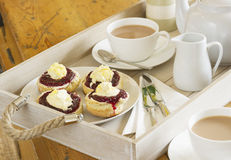 Cornish cream tea. Tea with home made scones topped with Cornish clotted cream and strawberry jam on a wooden tray Royalty Free Stock Photography