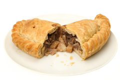 Cornish Pasty cut in half. Traditional Cornish pasty served on a white plate and cut in half - white background Stock Images