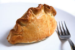 Cornish pasty meat pie and fork. A traditional British Cornish Pasty - a pastry case filled with a thick meat and potato stew - with a fork on a plate Royalty Free Stock Photography