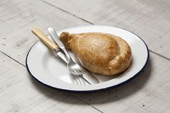 Cornish pasty on a white enamel plate. A cooked Cornish pasty meal on a white enamel plate with a knife and fork on a light coloured table top stock photos