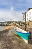 Cornish Pilot Gig on the quayside, St Ives, North Cornwall, UK. Freshly painted Cornish pilot gig, with view over the pretty fishing harbour of St Ives, on the royalty free stock image