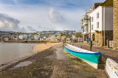 Cornish Pilot Gig, St Ives, North Cornwall, UK. Cornish pilot gig, with view over the pretty fishing harbour of St Ives, on the north Cornwall coast stock images