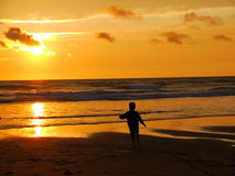 Cornish sunset. Child running on the beach as the sun goes down Royalty Free Stock Images