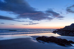 Cornish sunset panorama with fishing boat on distant tide, Cornw Stock Photography
