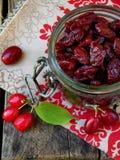 Corniso secado & x28; berry& x29 da cereja de cornalina; no frasco no fundo de madeira Imagem de Stock