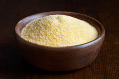 Cornmeal polenta in brown wooden bowl. Stock Image