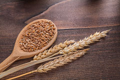 Corns в деревянных ушах ложки пшеницы на старой доске Стоковые Изображения