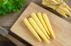 Corns и нож на разделочной доске Стоковые Изображения