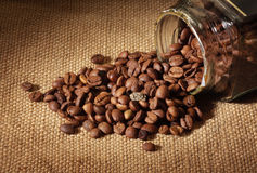 Corns of coffee. Glass jar. The corns of coffee are spilled on a table Stock Photo
