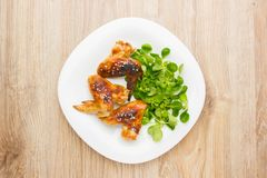 Fried chicken wings. Chicken wings of a barbecue on a white plate with salad. Cornsalad on a plate with wings. View from above stock images