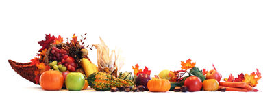 Cornucopia border. Thanksgiving cornucopia filled with autumn fruits and vegetables spread out to create a border Stock Photo