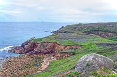 Cornwall coast near Mousehole. View across several kilometres of the southcoast of Cornwall near Mousehole with rocky cliffs and beach and grassy hills Royalty Free Stock Photo