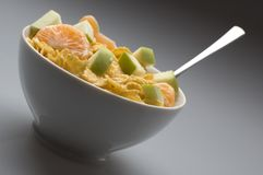 Corny. Bowl of yellow cornflakes with fruit close up Royalty Free Stock Photo