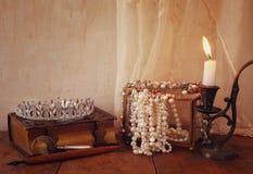 Coroa da rainha do diamante, pérolas brancas ao lado do livro velho Imagem de Stock