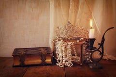 Coroa da rainha do diamante, pérolas brancas ao lado do livro velho Foto de Stock Royalty Free