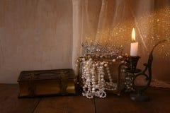 Coroa da rainha, pérolas brancas ao lado do livro velho Fotografia de Stock Royalty Free