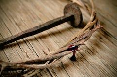 A coroa de espinhos de Jesus Christ e de um prego na cruz santamente Fotos de Stock