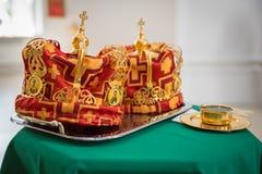 Coroas para o casamento em uma bandeja de prata e no copo dourado do vinho no clothc verde Fotos de Stock Royalty Free