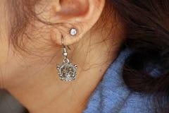 Coroe a forma do brinco do metal com o brinco do diamante na orelha de fotografia de stock