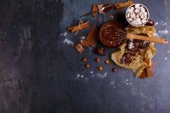 Corolla in een kop gesmolten chocolade en snoepjes naast een steenachtergrond royalty-vrije stock afbeelding