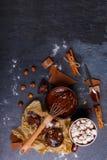 Corolla in een kop gesmolten chocolade en snoepjes zij aan zij Mening van hierboven stock foto
