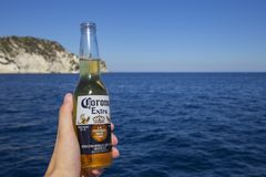 Corona beer bottle in hand. ZAKYNTHOS, GREECE - August 1, 2017: Corona beer bottle in hand on the sea stock image