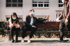 Corona - covid-19 social distancing concept picture with three people wearing face masks - stay away
