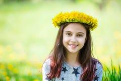 Corona d'uso della ragazza sveglia dei denti di leone e di sorridere Fotografie Stock