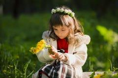 Corona d'uso della ragazza sveglia dei denti di leone e di sorridere mentre sedendosi sull'erba in parco Immagine Stock