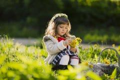 Corona d'uso della ragazza sveglia dei denti di leone e di sorridere mentre sedendosi sull'erba in parco Fotografia Stock