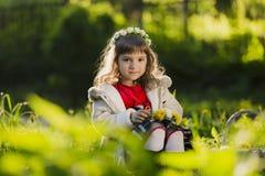 Corona d'uso della ragazza sveglia dei denti di leone e di sorridere mentre sedendosi sull'erba in parco Fotografie Stock Libere da Diritti