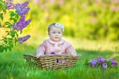 Corona d'uso di un anno sorridente del fiore della neonata 1-2, tenente mazzo del lillà all'aperto esaminando macchina fotografic Fotografie Stock