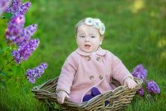 Corona d'uso di un anno sorridente del fiore della neonata 1-2, tenente mazzo del lillà all'aperto esaminando macchina fotografic Immagine Stock