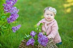 Corona d'uso di un anno sorridente del fiore della neonata 1-2, tenente mazzo del lillà all'aperto esaminando macchina fotografic Fotografie Stock Libere da Diritti