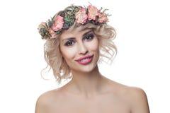 Corona de las flores de la mujer que lleva modelo feliz hermosa aislada en el fondo blanco Pelo rizado, maquillaje y flores fotografía de archivo
