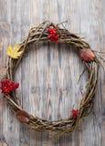 Corona dei ramoscelli su una vecchia porta di legno con le bacche di autunno e la a Fotografie Stock