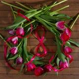 Corona dei tulipani, nastro rosso su fondo di legno Immagine Stock