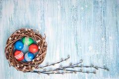 Corona del salice di Pasqua ed uova di Pasqua variopinte su fondo blu Copi lo spazio Fotografia Stock