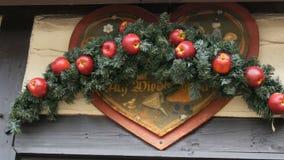 Corona dell'abete di Natale con le mele rosse sopra l'entrata da immagazzinare del mercato tedesco di Natale, con l'iscrizione de video d archivio
