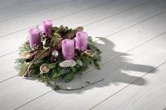 Corona di arrivo con le candele porpora Fotografie Stock