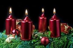 Corona di arrivo con quattro candele brillanti Fotografia Stock