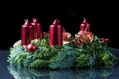 Corona di arrivo con quattro candele rosse Fotografia Stock