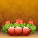Corona di arrivo dei ramoscelli con le candele rosse ed i vari ornamenti Immagine Stock
