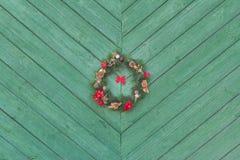 Corona di arrivo di Holyday di Natale che appende fuori al fondo di legno verde della porta Fotografie Stock