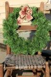Corona di festa che pende dalla vecchia sedia di canna Immagine Stock